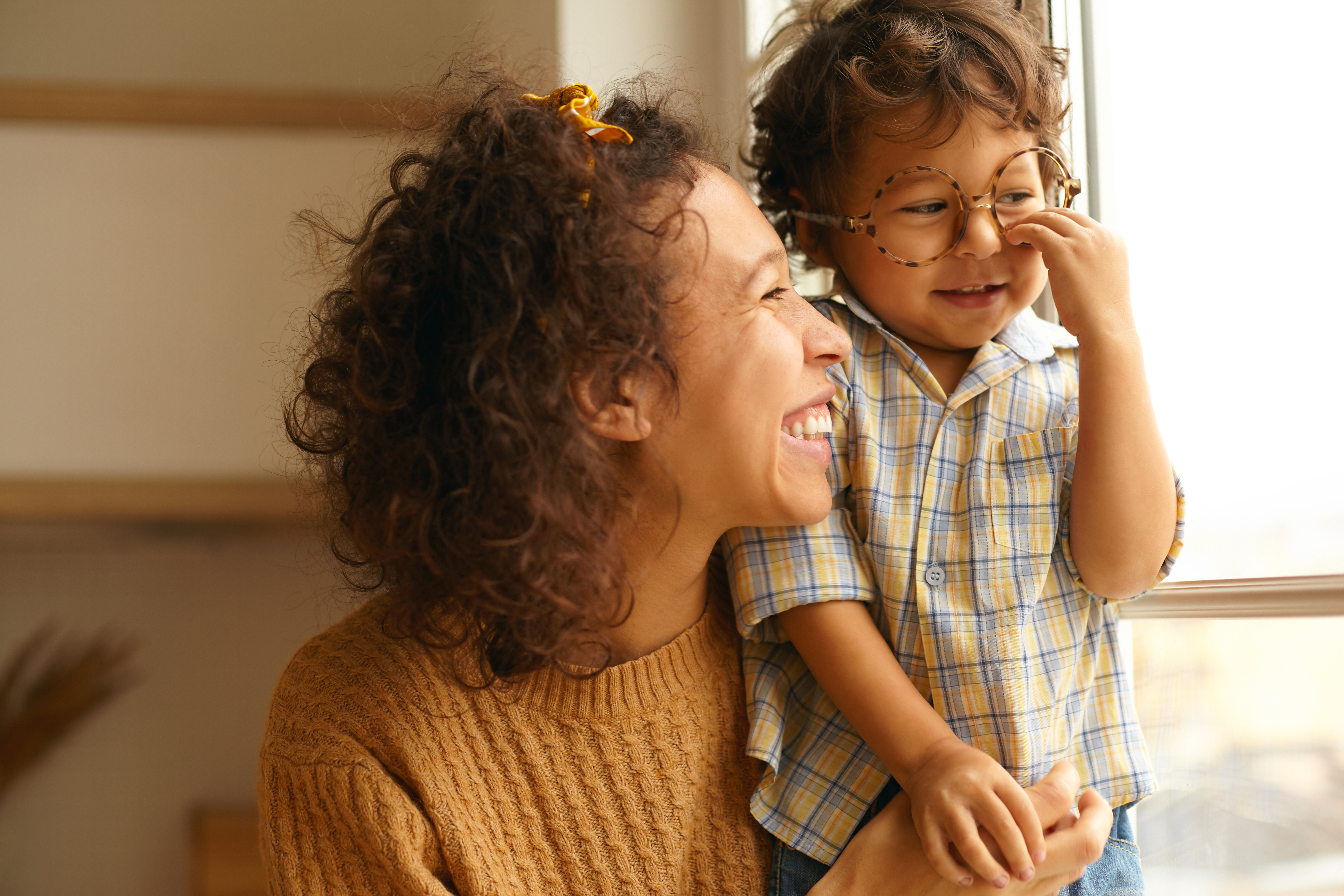 close-up-image-of-happy-young-wavy-haired-hispanic-female-posing-by-window-embracing-baby-son-cute-three-year-old-boy-wearing-round-eyeglasses-spending-day-at-home-family-and-relationships