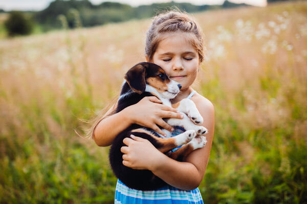 little-girl-holds-puppy-on-her-arms